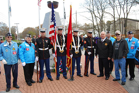 Mayor Allan M. Dorman (fourth from right) poses in front of the Islandia Veterans Memorial with local war veterans and members of The United States Marine Corps at the village's Veterans Day ceremony on November 10.