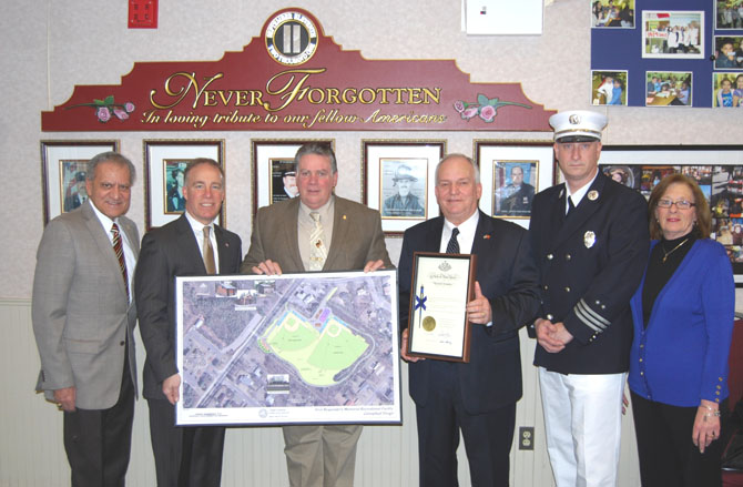 Suffolk County Legislator Tom Cilmi (second from left) and New York State Assemblyman Al Graf (third from left) hold up a rendering of the Village of Islandia First Responders Memorial Recreational Field while Mayor Allan M. Dorman (third from right), Village of Islandia, displays a certificate from New York Governor Andrew Cuomo's office which grants ownership of the ball field to the village. Also pictured (l-r): Suffolk County Legislator Tom Muratore and Islandia Village Trustees Michael Zaleski and Patty Peters.