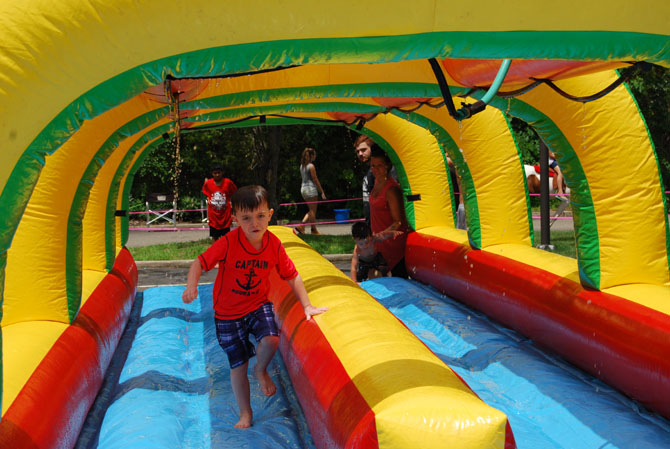 Gavin Schrage cools off as he runs through the water slide during the Village of Islandia's 12th annual Bar-B-Que, which was held on July 15.