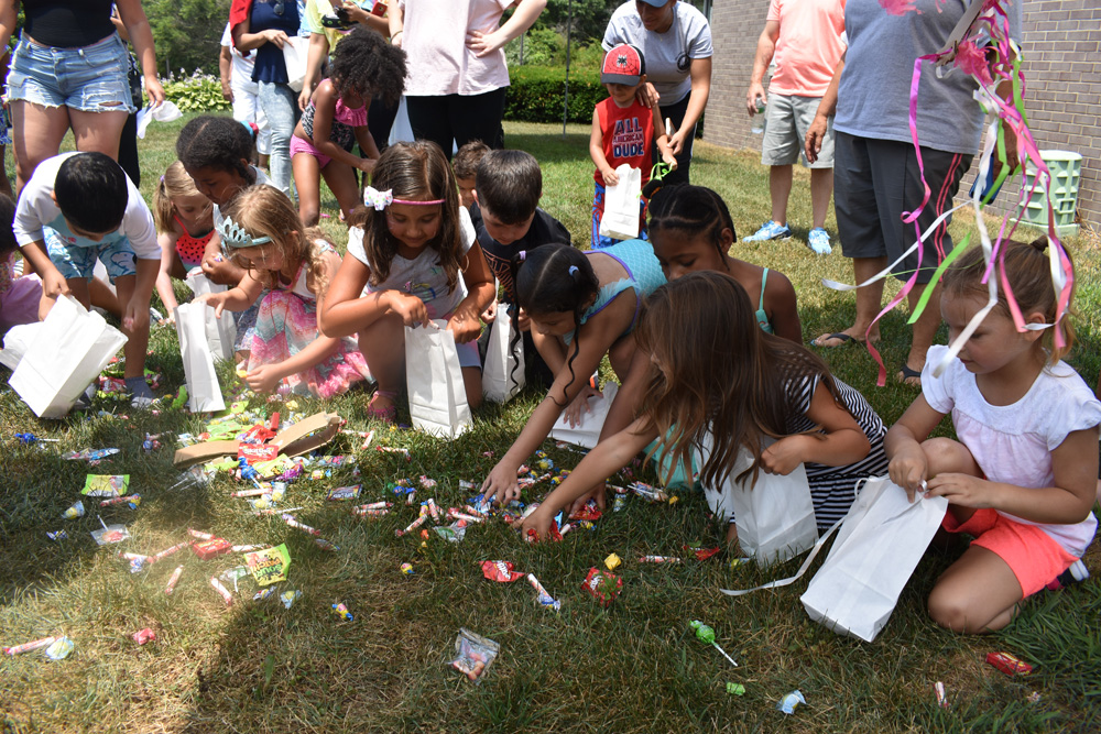 Children collect candy after breaking open the piñata at the Village of Islandia's 13th Annual Bar-B-Que on July 14.