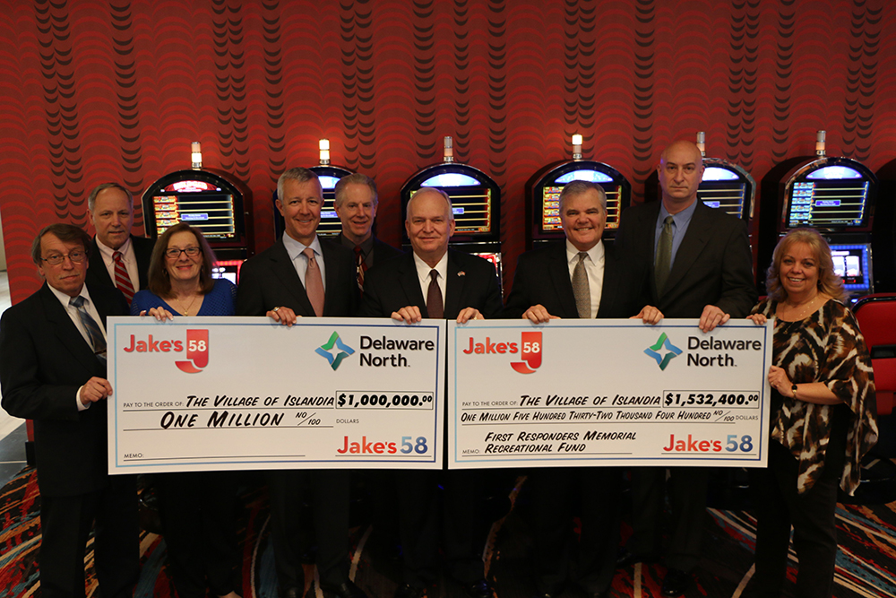 Pictured is Mayor Allan M. Dorman (fourth from right) along with members of the Islandia Village Board of Trustees holding the two checks from Delaware North in the amounts of $1 million and $1,532,400 at a special ceremony at the Islandia Marriott Hotel (Jake's 58) on February 8. Also pictured (left to right): Gerry Peters, Village Building Inspector; Joseph Prokop, Village Attorney; Patty Peters, Village Trustee; Louis M. Jacobs, Co-Chief Executive Officer, Delaware North; Chuck Kilroy, General Manager, Islandia Marriott Hotel (Jake's 58); Brian Hansberry, President of Gaming, Delaware North; Michael Zaleski, Deputy Mayor, Village of Islandia; and Barbara Lacey, Village Trustee.