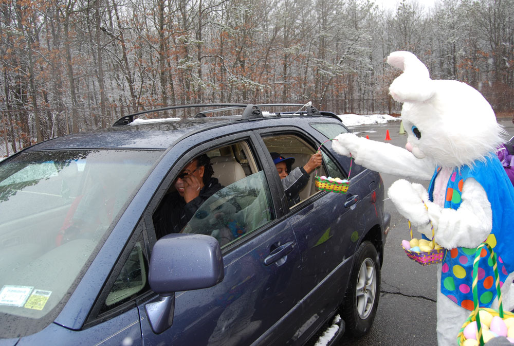 The Easter Bunny hands out a basket full of eggs to a child at the Village of Islandia's drive-through Easter event on March 28.