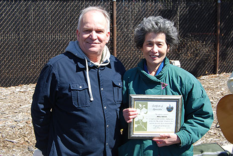 Mayor Allan M. Dorman (left) presents a certificate of appreciation to village resident Shy Main Shieh (right) in recognition of her volunteer work at all of the village's events at the 8th Annual Easter Egg Hunt on March 23.