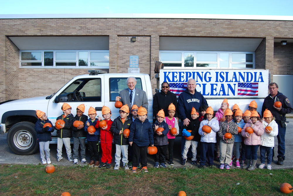 Joining the students at Andrew T. Morrow Elementary School with their pumpkins are (standing, left to right) Dr. Howard Koenig, Superintendent of Schools, Central Islip Union Free School District; Dr. Neema Coker, Principal, Andrew T. Morrow Elementary School; Allan M. Dorman, Mayor, Village of Islandia; and Gerald Peters, Building Inspector, Village of Islandia. The pumpkins were donated by the Village.