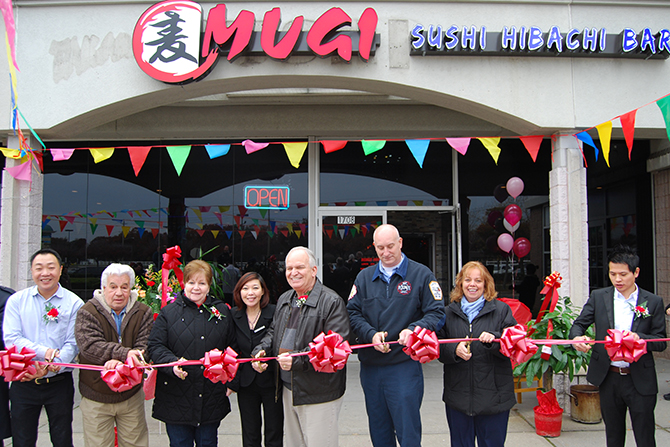 Mayor Allan M. Dorman (third from right), Village of Islandia, prepares to cut the ribbon in celebration of the grand opening of Mugi Sushi Hibachi & Bar with village officials and Mugi's owners and managers on November 16.