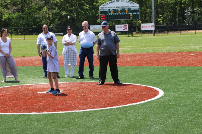 Allan M. Dorman (right), Mayor, Village of Islandia, watches Collin throw out the first pitch to commemorate the grand opening of the First Responders Recreational Ball Field on June 2. Also pictured (left to right): Denise Schrage, Commissioner of Parks and Recreation, Village of Islandia; Harry Singh, Chief Executive Officer, Bolla Market; Kamljit Singh; and Chuck Kilroy, Suffolk President and General Manager, Jake's 58.