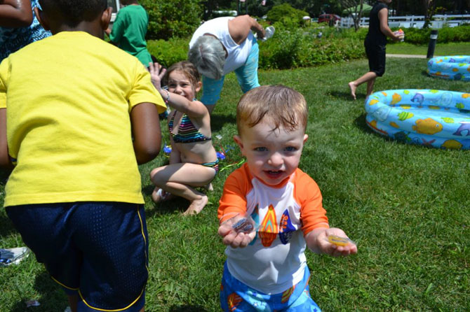 Two-year-old Gavin Schrage shows off the two pieces of candy that he received from the piñata at Islandia Village's 9th annual BBQ.