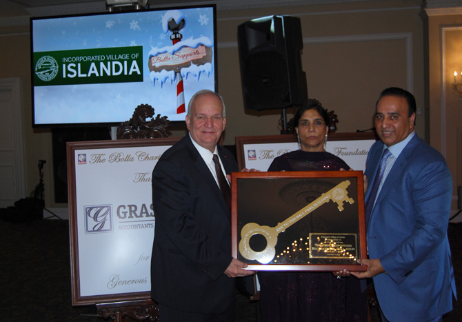 Mayor Allan M. Dorman (left) accepts an award from Kamljit Singh (center) and Harry Singh (right) of the Bolla Charity Foundation during the organization's Second Annual Gala at Oheka Castle on December 7.