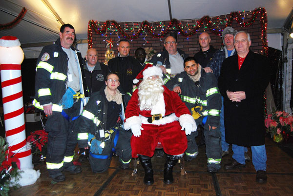 Islandia Village Mayor Allan M. Dorman (front row, right) is joined by Mike Zaleski (back row, second from right), Santa Claus and members of the Central Islip Fire Department during the village's 8th annual Christmas tree lighting ceremony on December 7.