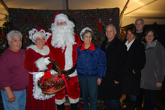 """Islandia Village Mayor Allan M. Dorman (fourth from right) is joined by Santa Claus and village officials at the 9th annual Christmas tree lighting ceremony on December 6. Also pictured (l-r): Tony Church, Village Administrator; Barbara Lacey, Trustee, as """"Mrs. Claus""""; Shy Main Shieh, Event Volunteer and Islandia resident; Diane Olk, Deputy Mayor; and Mike Zaleski and Patty Peters, Trustees."""