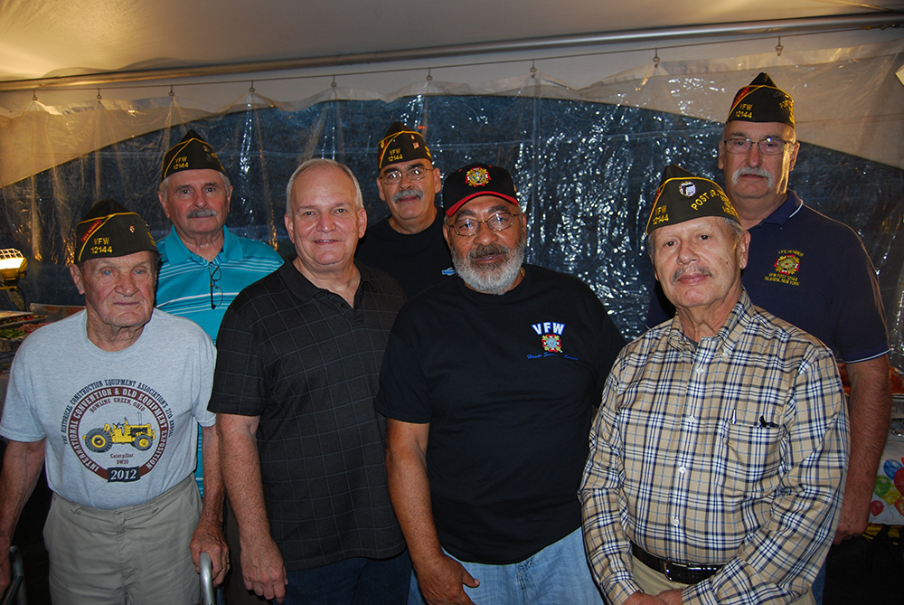 Mayor Allan M. Dorman (front row, second from left), Village of Islandia, honored local residents Victor Montanez (front row, second from right) and Raul Jimenez Cintron (front row, right) at a special ceremony on September 7 for their volunteer work in the community and in helping their fellow veterans. They are joined by members of Col. Francis S. Midura Veterans of Foreign Wars Post #12144, including John Probst (front row, left) and (back row, l-r) Chaplain Tom Brauner, Eusebro Soto, Jr. and Post Commander Raymond Bush.