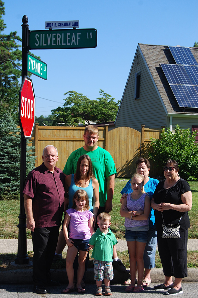 Mayor Allan M. Dorman (left), Village of Islandia, is joined by the family of Linda Sheahan, former Islandia Village Court Clerk, at a ceremony renaming Silverleaf Lane in her honor. Also pictured (l-r): Denise Schrage, Ms. Sheahan's daughter; Alyssa Schrage, Ms. Sheahan's granddaughter; Deputy Village Clerk Marilyn Griffaton and Florence Barrett, Ms. Sheahan's sisters. Standing in front of Ms. Schrage are Sophia Schrage (left) and Gavin Schrage (right), Ms. Sheahan's grandchildren. Standing behind Ms. Schrage: Justin Hinte, Ms. Sheahan's grandson.