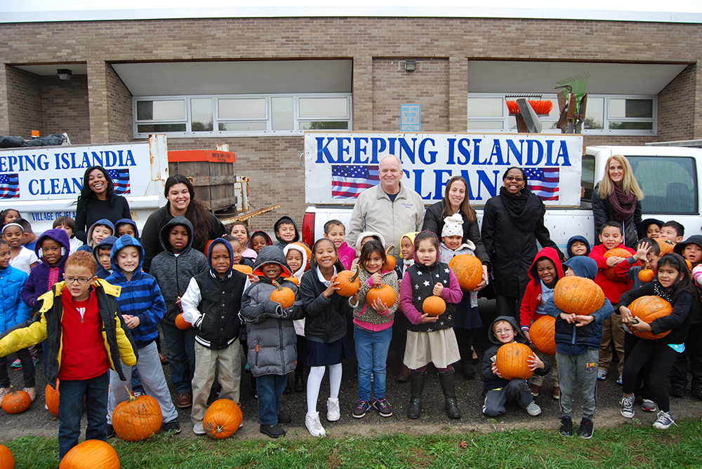 Joining the students at Andrew T. Morrow Elementary School with their pumpkins are Mayor Allan M. Dorman (back row, third from left), Village of Islandia, Denise Schrage (third from right), Village Activities Director, and Dr. Neema Coker (second from right), Principal, Andrew T. Morrow Elementary School. The pumpkins were donated by the Village.