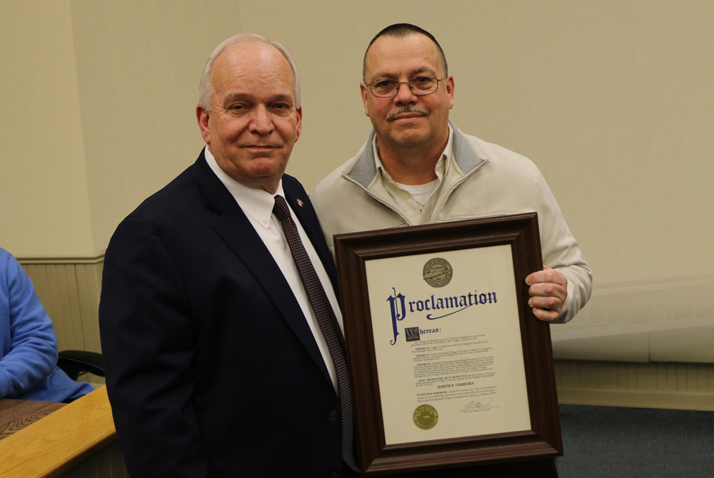 Mayor Allan M. Dorman (left), presents a proclamation to Joe Correira (right) for having served for nearly 25 years as Village Fire Marshal during a special ceremony at Village Hall on January 29.