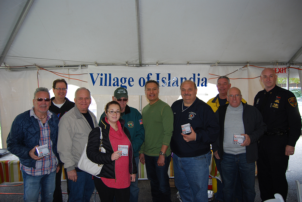 Allan M. Dorman (third from left), Mayor, Village of Islandia, is joined by Village residents who received free smoke detectors as part of the Village's commemoration of National Fire Prevention Month during the Pancake Breakfast with the Mayor on October 29. Also pictured are Jesse Walia (fifth from right), Owner, Dunkin' Donuts of Islandia; Robert Sutton (fourth from right), Fire Prevention Officer, Central Islip Fire Department; Kevin McCarroll (third from right), Safety Officer, Central Islip Fire Department; and Michael Zaleski (right), Fire Marshal, Village of Islandia.