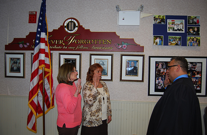 Phil Goglas (right), U.S. District Court Judge, swears in Patty Peters (left) and Barbara Lacey (center) for another term as Village Trustees at the Village Board meeting on April 7.