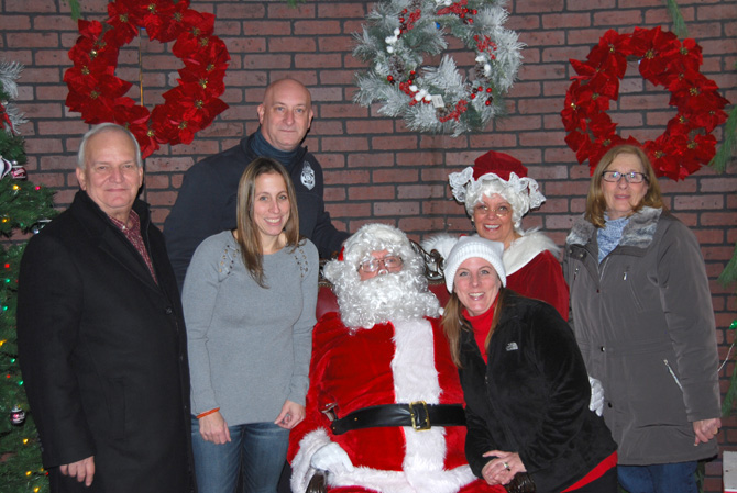 "Islandia Village Mayor Allan M. Dorman (left) is joined by Santa Claus (center, seated) and Village Trustees and staff members at the 12th Annual Christmas Tree Lighting on December 2. He is joined by (left to right) Denise Schrage, Village Activities Director; Carrie Hays, Ms. Schrage's sister; ""Mrs. Claus"" Barbara Lacey, and Patty Peters, Village Trustees. Standing behind Ms. Schrage: Michael Zaleski, Deputy Mayor."