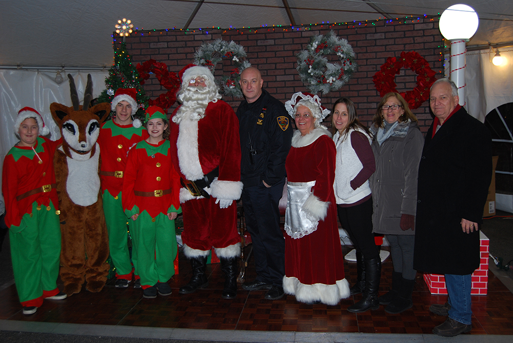 "Islandia Village Mayor Allan M. Dorman (right) is joined by Santa Claus (fifth from left), Rudolph the Red-Nosed Reindeer (second from left), Santa's elves and village officials at the eleventh annual Christmas tree lighting ceremony on December 10. Also pictured: Michael Zaleski (fifth from right), Deputy Mayor; ""Mrs. Claus"" Barbara Lacey (fourth from right), Trustee; Denise Schrage (third from right), Village Activities Director; and Patty Peters (second from right), Trustee."