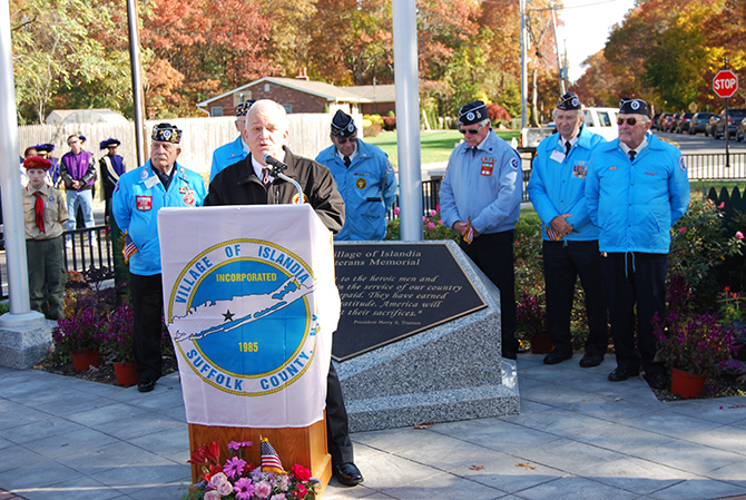 Mayor Allan M. Dorman (behind podium) speaks to the attendees at the Veterans Day ceremony at the Veterans Memorial Triangle on November 8 as members of the Central Long Island chapter of the Korean War Veterans Association look on.