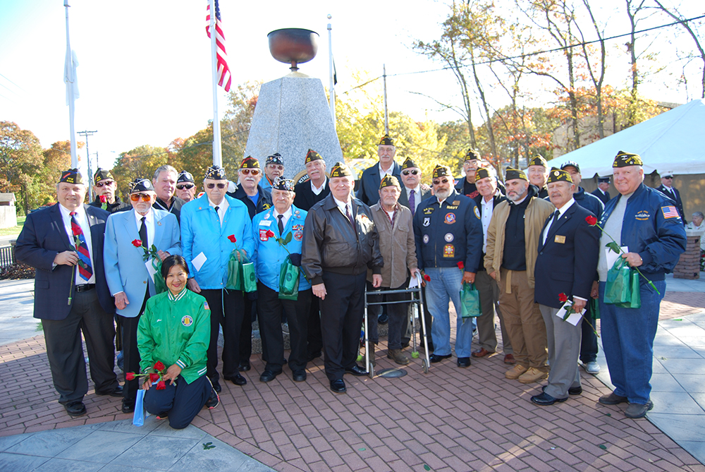 Mayor Allan M. Dorman (front row, center) poses with the members of the Col. Francis S. Midura Veterans of Foreign Wars Post #12144, the Central Long Island Chapter of the Korean War Veterans Association and other war veterans at the Village of Islandia's Veterans Day ceremony on November 5. He is also joined by New York State Assemblyman Al Graf (back row, third from left) and Gina Lekstutis (kneeling), Owner, Gina's Flower Shoppe.