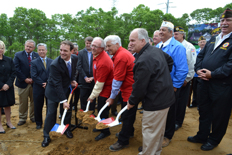 Mayor Allan M. Dorman (right) breaks ground with a ceremonial shovel at the proposed Veterans Way subdivision on May 23. He is joined by (left to right): Adam Famularo, General Manager, Cloud Computing Business, CA Technologies; Edgar Goodale, Chairman, and Tom Datre, President, Long Island Home Builders Care Development Corp.