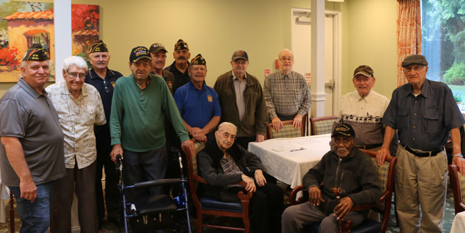 "Allan M. Dorman (standing, front row, left), Mayor, Village of Islandia, and Raul Jimenez Cintron (standing, front row, fourth from left), Commander, Col. Francis S. Midura Veterans of Foreign Wars Post #12144, are joined by local war veterans and members of VFW Post #12144 at the Arbors Assisted Living at Islandia West during the ""Vets' Chat"" on July 24."