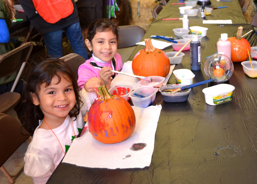 The children of Islandia Village join their parents in decorating their pumpkins at the Village of Islandia's 7th Annual Pumpkin Fest.