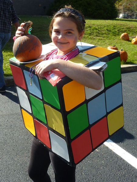 One of the children dressed as a Rubik's cube displays a pumpkin she decorated.