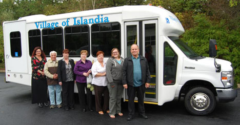 Islandia Village employees pose in front of the bus that the village recently purchased for senior citizens who need transportation.