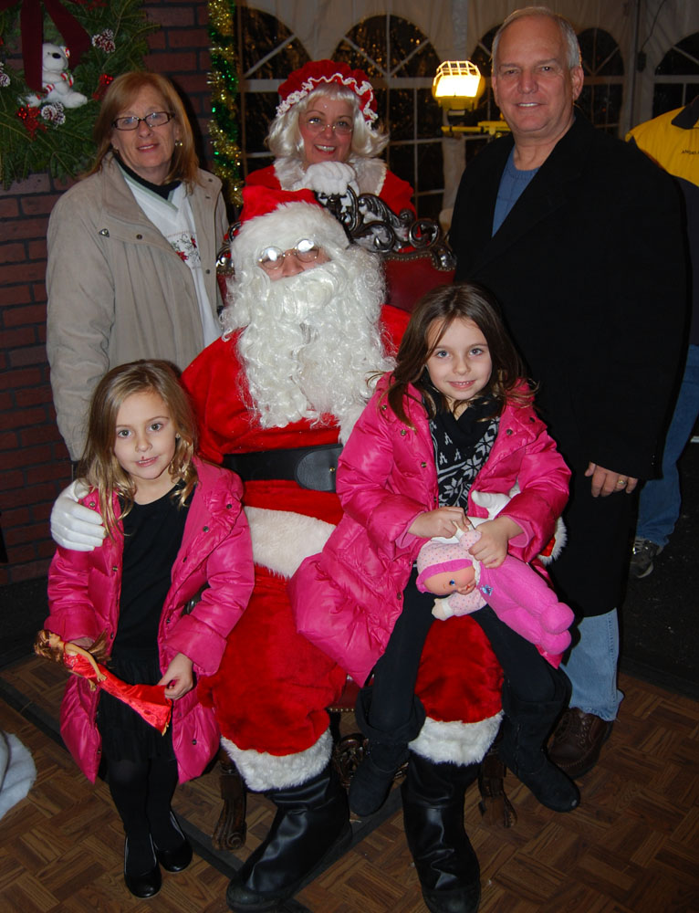 """Islandia Village Trustees Patricia Peters (back row, left) and Barbara Lacey as """"Mrs. Claus"""" (back row, center) and Mayor Allan Dorman (back row, right) pose with Santa Claus at the village's 6th annual Christmas tree lighting ceremony. They are also joined by Abigail and Holly Neri, whose family helped light the tree."""
