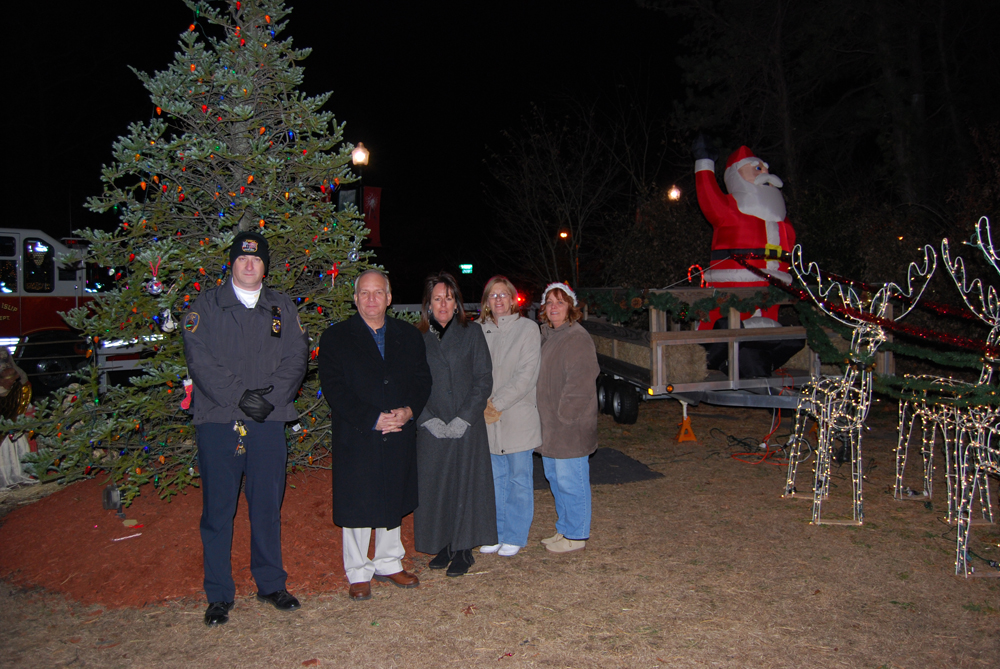 Islandia Village Mayor Allan Dorman (second from left) and Deputy Mayor Diane Olk (center) pose in front of the village's Christmas tree after the tree lighting ceremony.
