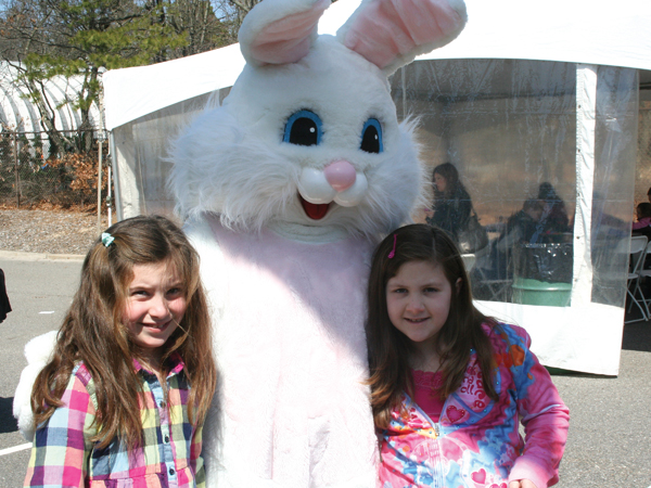 Two children pose with the Easter Bunny at the 5th Annual Easter Egg Hunt at Islandia Village Hall on March 27.