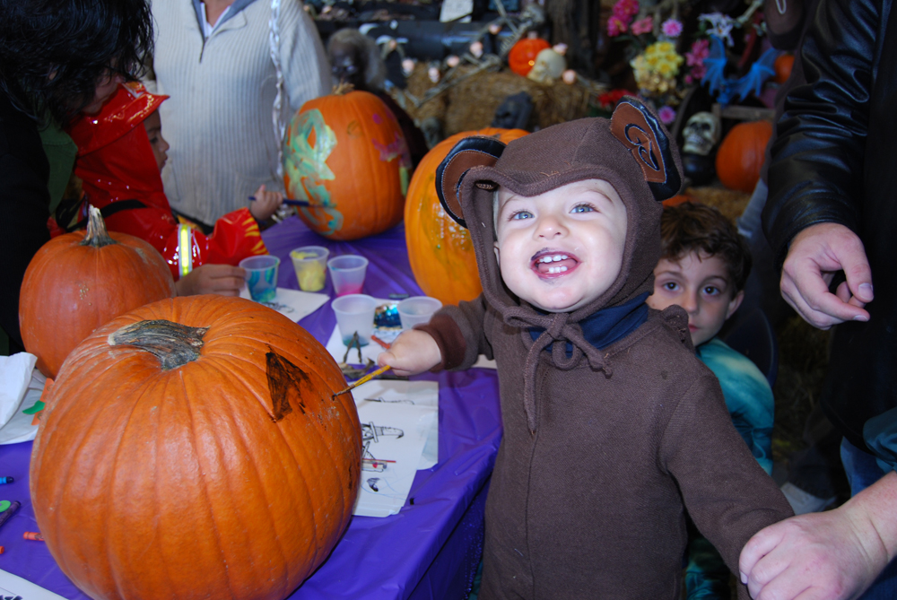 18-month-old Vito Sacino, son of Vito and Krista Sacino of Islandia, is dressed up in costume and touched up with some paint from kissing the pumpkin he just painted at Islandia Village's Fourth Annual Craft Fair and Pumpkin Fest.