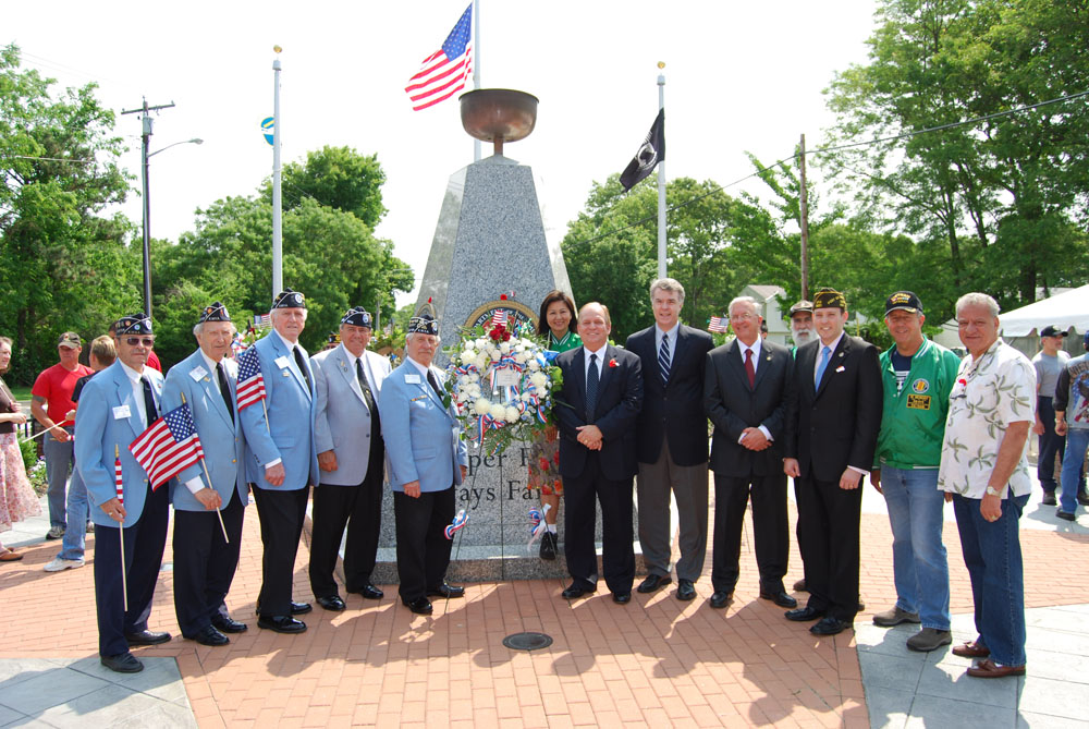 Allan Dorman (center, right), Mayor, Islandia Village, is joined in front of local war veterans and elected officials in front of the memorial after the village's Memorial Day ceremony.