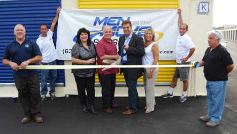 Mayor Allan M. Dorman (fourth from left) and John Beyer (fourth from right), President, Men On The Move, join in cutting the ribbon in celebration of Men On The Move's grand opening.