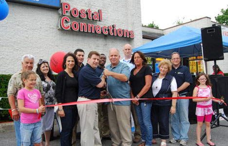 Standing behind the ribbon (left to right): Tony Church, Highway Commissioner, and Audrey Giordano; Teresa Colabella, Co-Owner, Eric Molina, Assistant Manager, Louis Colabella, Co-Owner and Raisson Elliott, Assistant Manager, Postal Connections; Allan M. Dorman, Mayor; Mike Zaleski, Trustee; Diane Olk, Deputy Mayor; Jerri Bixon, Broker, Brown Harris Stevens; Ralph Fiorillo, Manager, Postal Connections. Holding the ribbon are Mr. Fiorillo's daughters, Christie Snyder (left) and Jeanna Fiorillo (right).