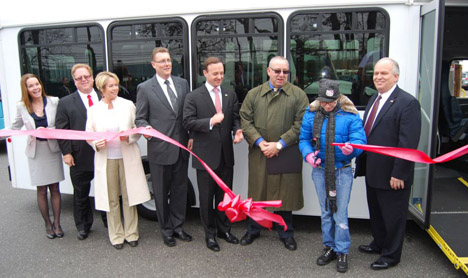 Islandia Village Mayor Allan M. Dorman (right) watches Helen Robacker (second from right) cut the ribbon to introduce the new handicapped-accessible bus Rides Unlimited of Nassau & Suffolk received on February 29.