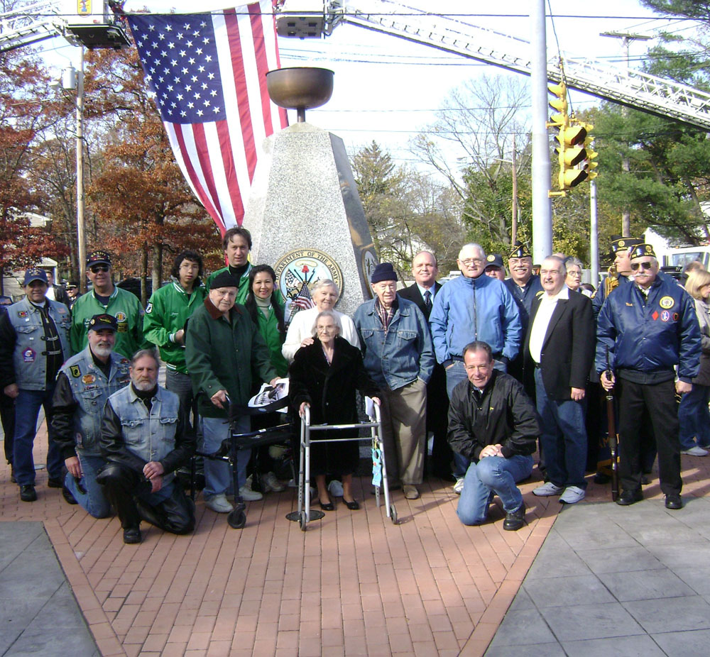 Islandia Village Mayor Allan Dorman (fifth from right) poses with local war veterans and residents from The Arbors Assisted Living in front of the Islandia Village War Veterans Memorial.