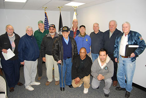 Mayor Allan M. Dorman (back row, third from right) poses with local war veterans inside the Village of Islandia Commons, where the mayor announced plans to establish a Veterans of Foreign Wars post in the village.